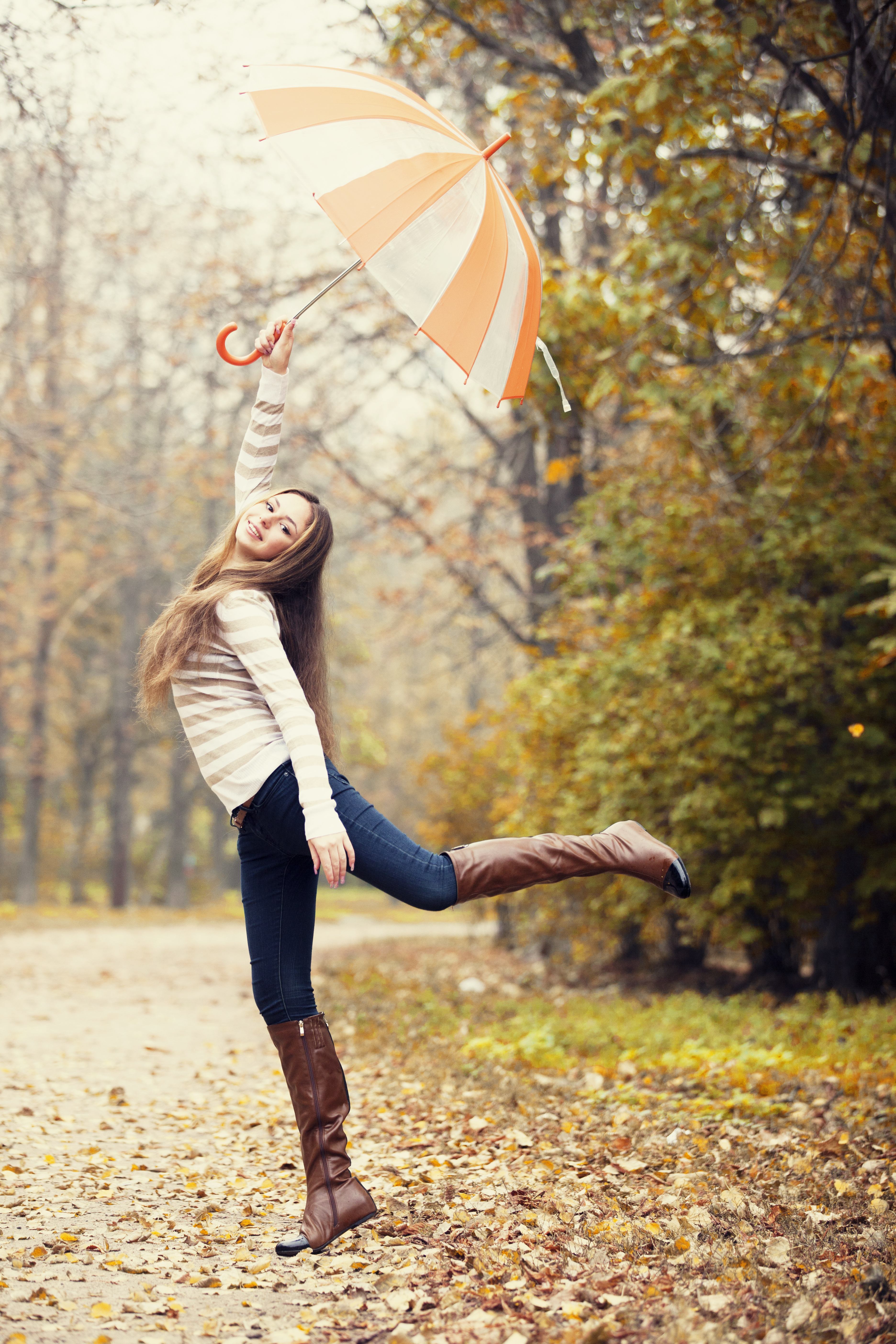 Beautiful girl with umbrella at autumn park.